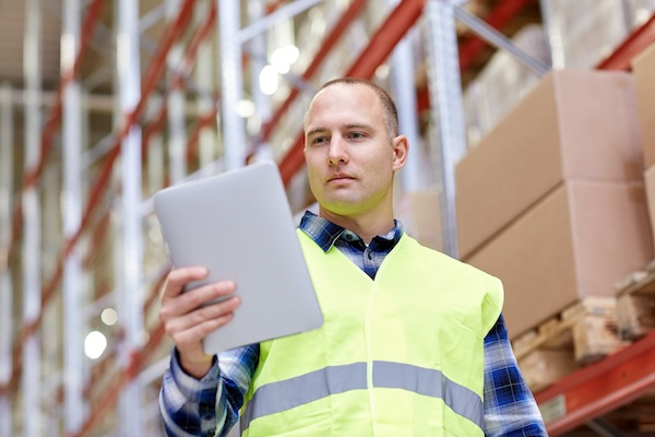 wholesale, logistic, technology, shipment and people concept - man or manual worker with tablet pc at warehouse