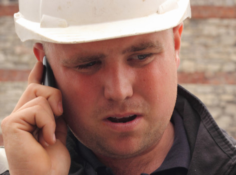 A construction worker uses a mobile phone.