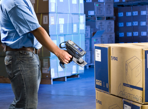 Warehouse worker scanning box with a mobile device.